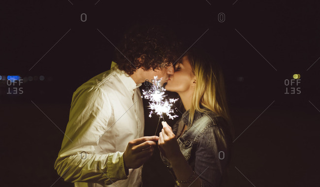 Kissing young couple holding sparklers on the beach at night