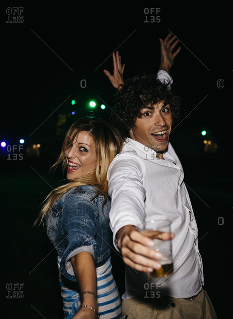 Happy young couple dancing back to back at summer night festival