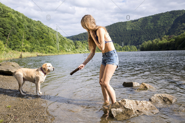 Young woman playing with her dog in a lake