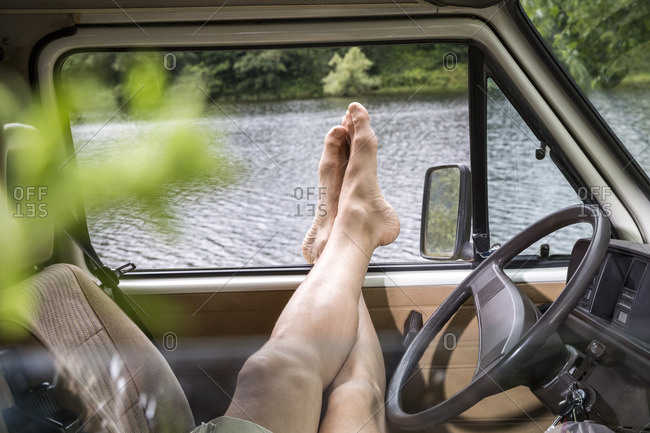 Legs of a man relaxing in a van at lakeside
