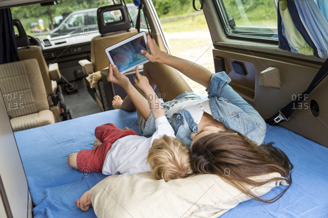 Mother and son lying on mattress in van using tablet