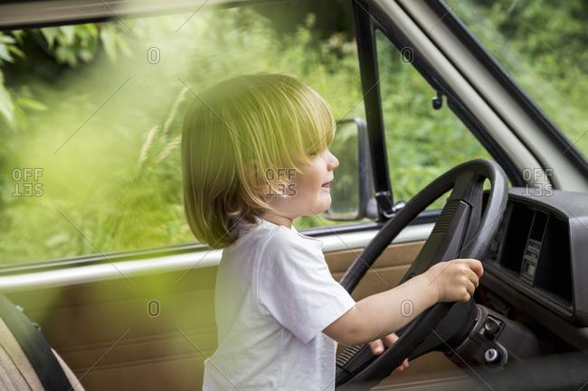 Toddler sitting at steering wheel of a van