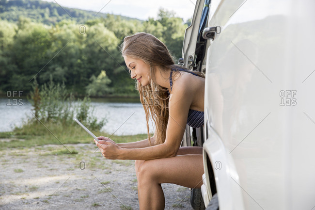 Young woman sitting in a van at lakeside using digital tablet