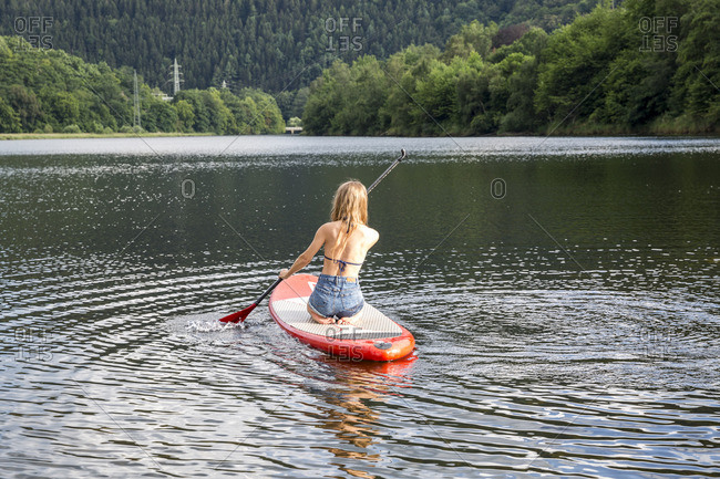 Young woman paddle boarding in a lake