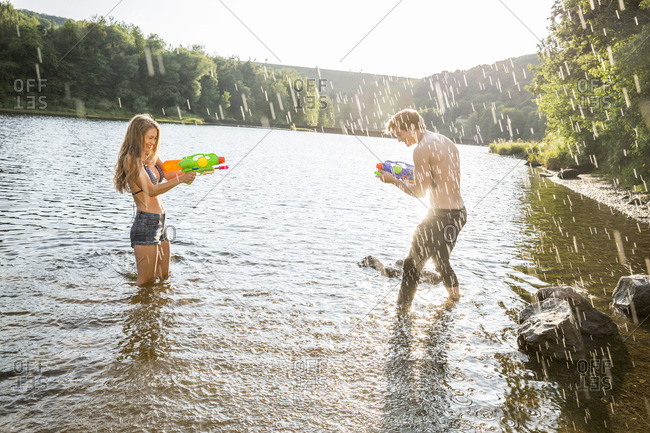Young couple in a lake splashing with water guns
