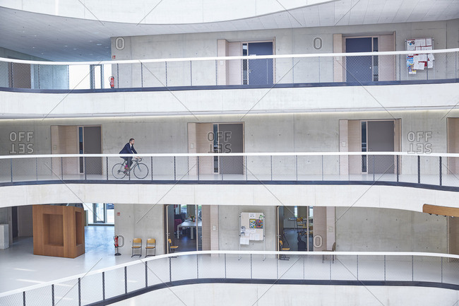 Businessman riding bicycle in modern office building
