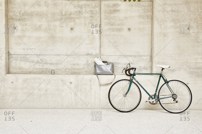 Bicycle at concrete wall and bag in ledge