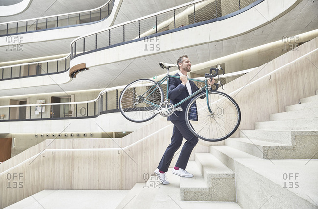 Businessman carrying bicycle in modern office building