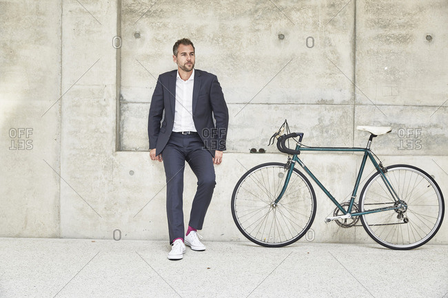 Businessman with bicycle at concrete wall