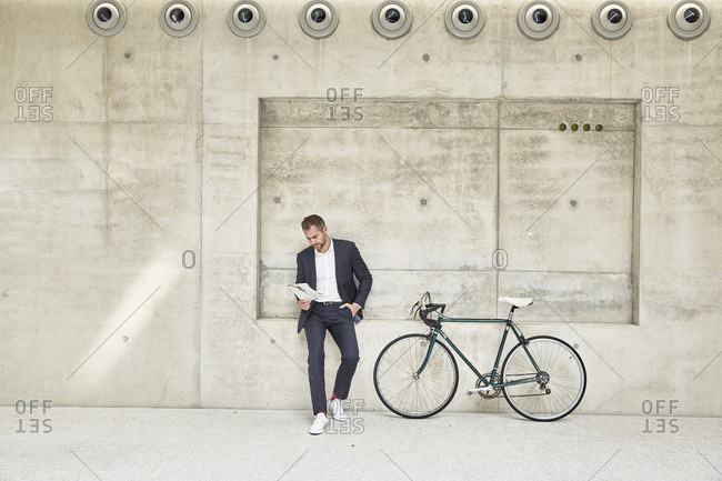 Businessman with bicycle at concrete wall reading document