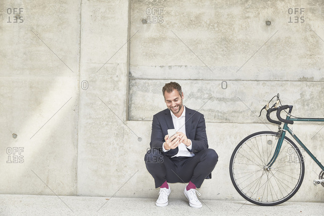 Smiling businessman with bicycle at concrete wall looking at cell phone