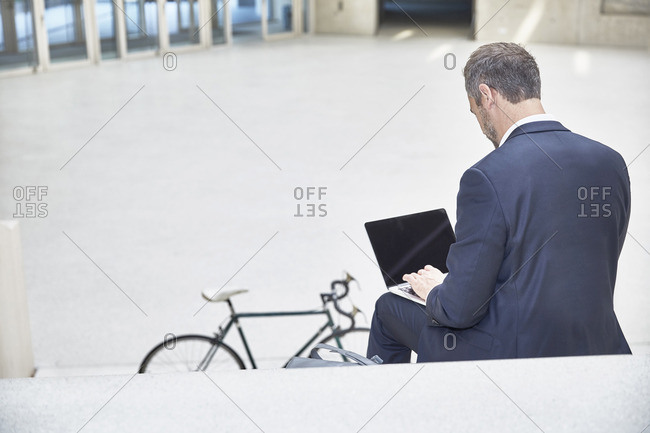 Businessman on stairs using laptop