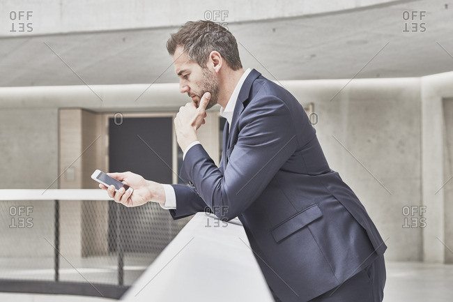 Businessman in office building looking at cell phone