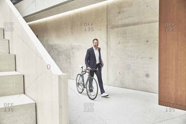 Businessman pushing bicycle along concrete wall