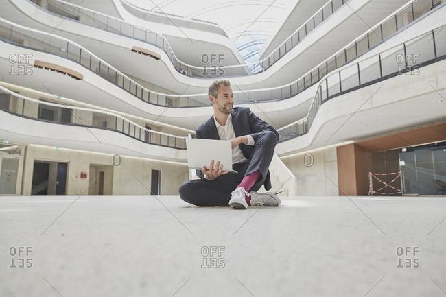 Businessman sitting on floor in office building using laptop