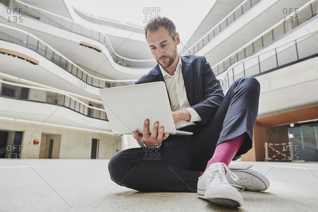 Businessman sitting on floor in office building using laptop