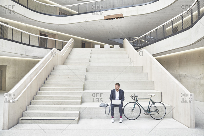 Businessman on stairs using laptop next to bicycle