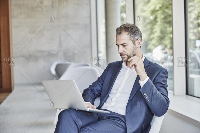 Businessman sitting using laptop - Offset