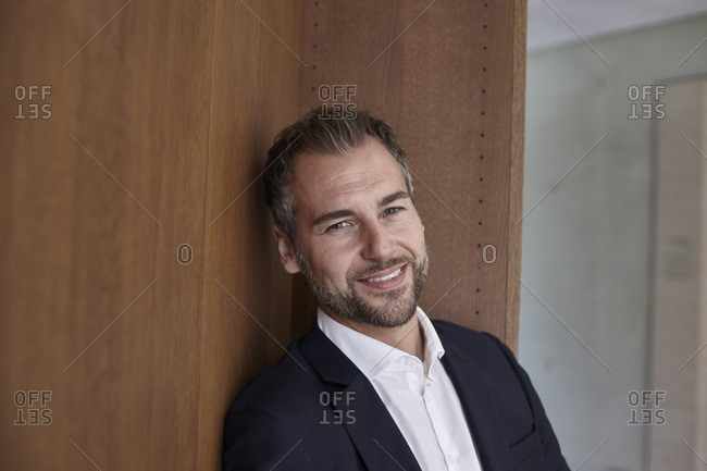 Portrait of smiling businessman at wooden wall