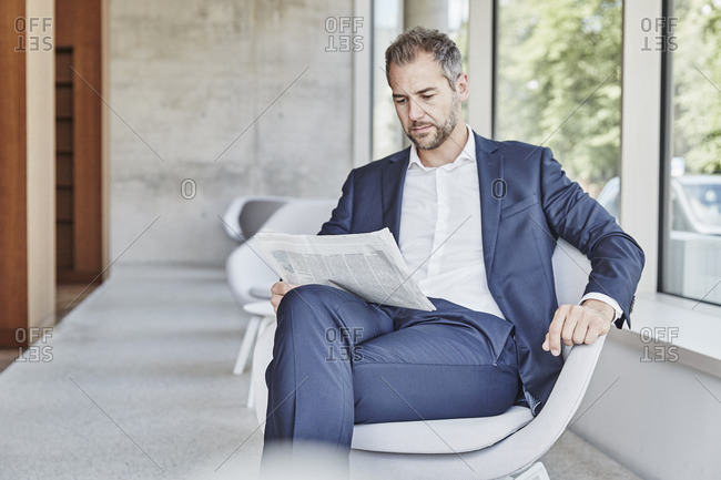 Businessman sitting on chair reading newspaper