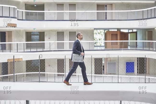 Businessman walking with bag in modern office building