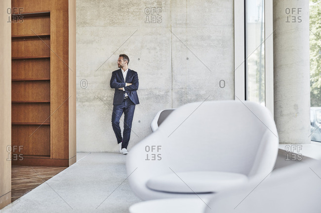 Businessman leaning against concrete wall