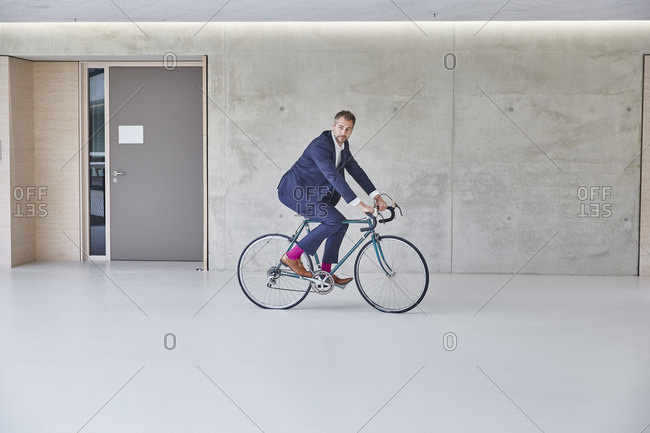 Businessman riding bicycle in office building