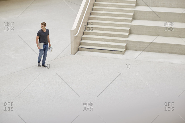 Young man with laptop and documents walking in foyer