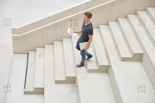Young man with laptop and documents walking on stairs