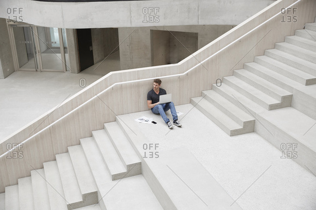 Young man sitting on stairs in office building using laptop
