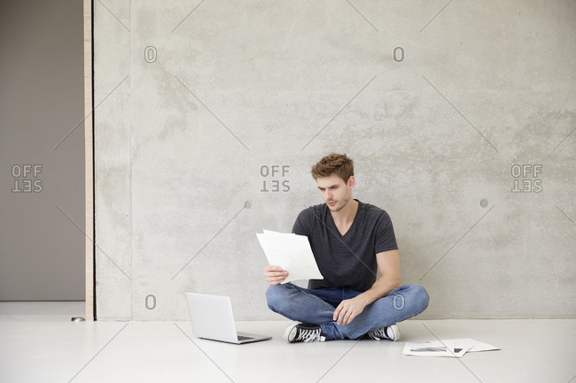 Young man sitting on floor reading documents