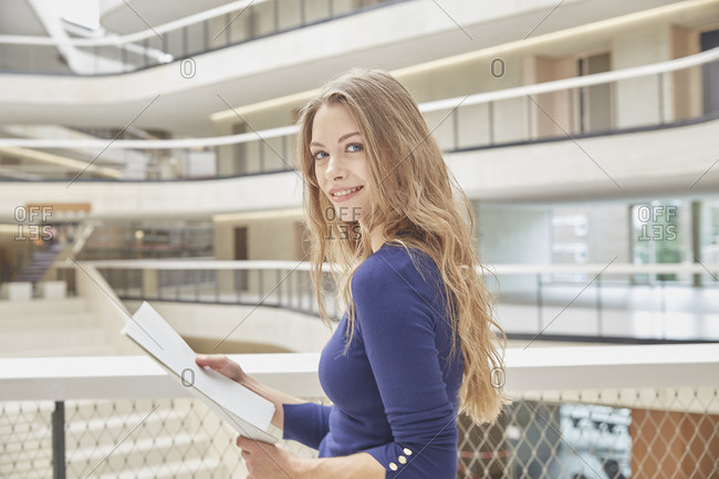 Portrait of smiling young woman holding folder