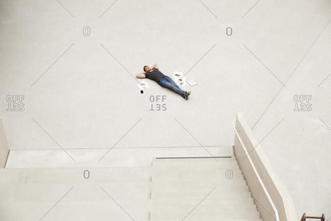 Young man lying on floor surrounded by papers