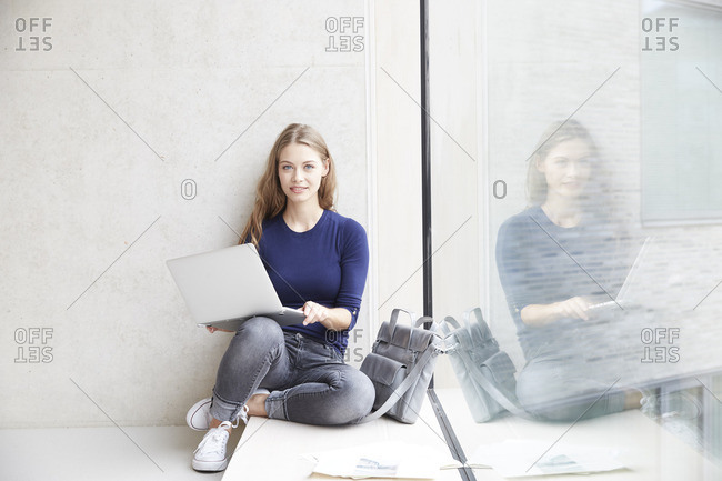 Smiling young woman with laptop at concrete wall