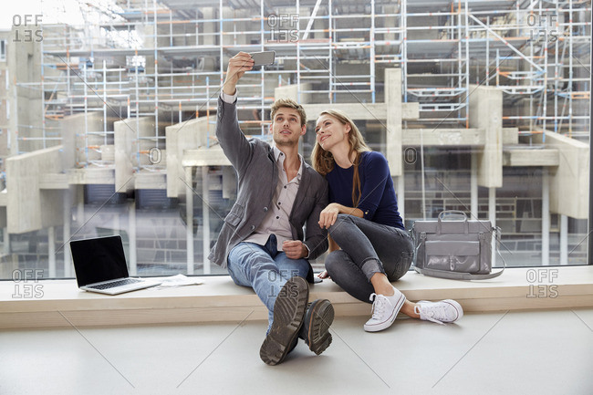 Young couple sitting at the window taking a selfie