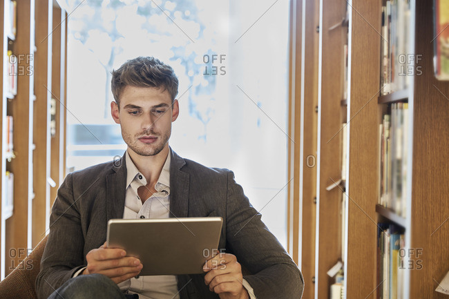 Young man using tablet in library