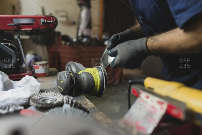 Forger treating metal in workshop