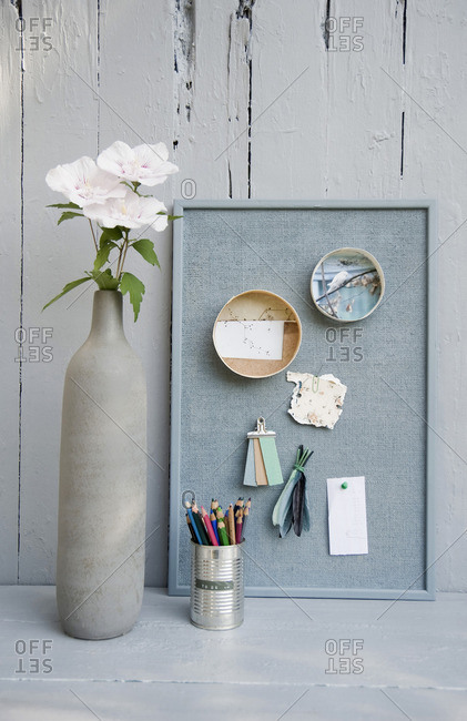 Mood board with photos,colored pencils, hibiscus blossoms, vase