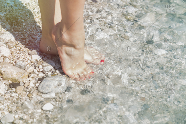 Feet of young woman at edge of water