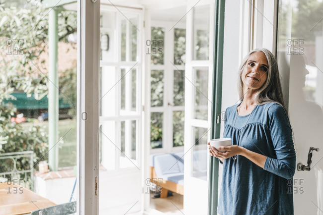 Smiling woman leaning at door frame of her winter garden with cup of coffee