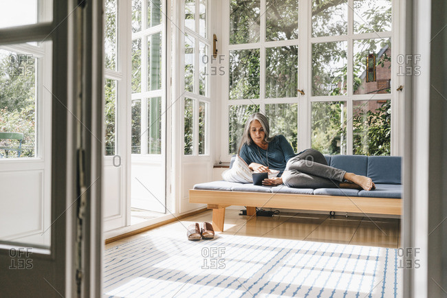 Woman lying on lounge in winter garden reading e-book