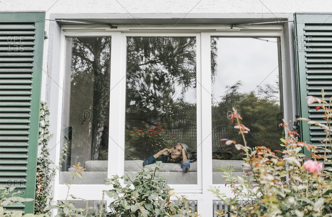 Woman on the phone behind window of a residential house