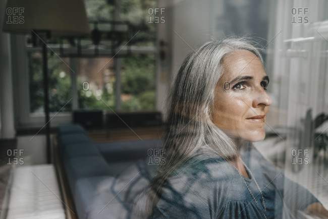 Woman at home looking through windowpane