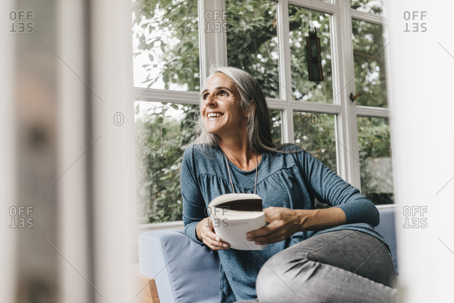 Smiling woman with book sitting on lounge in winter garden looking through window