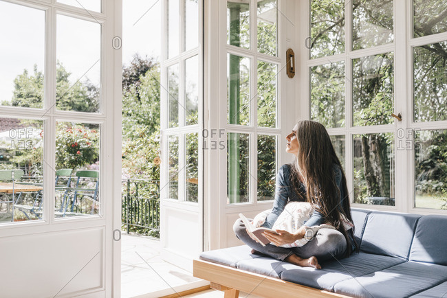 Woman sitting with book on lounge in winter garden looking through opened terrace door