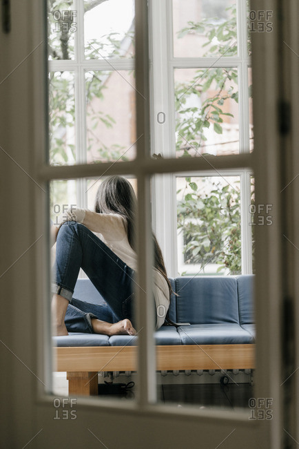 Back view of woman sitting on lounge in winter garden looking through window