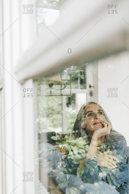 Smiling woman sitting behind windowpane looking at distance