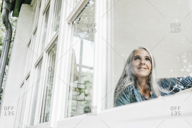 Smiling woman at home looking through window