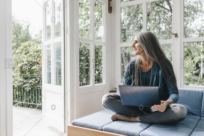 Woman with laptop sitting on lounge in winter garden looking through opened terrace door