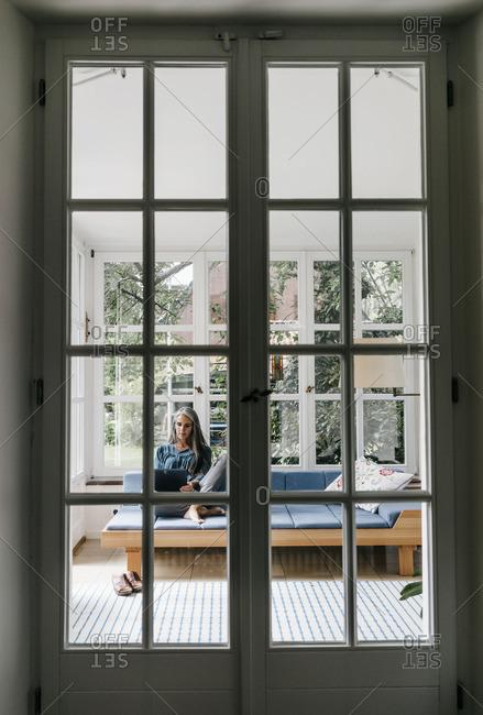 Woman sitting on lounge in winter garden using laptop